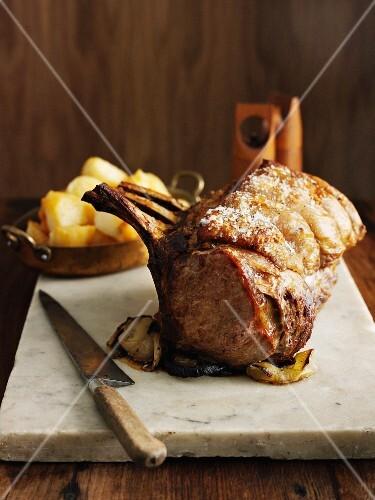 A rack of roast beef with roast potatoes