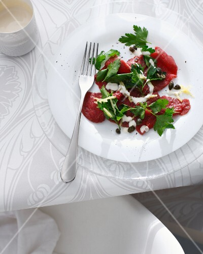 Plate of beef carpaccio on table