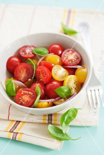 Colourful cherry tomato salad with onions and basil