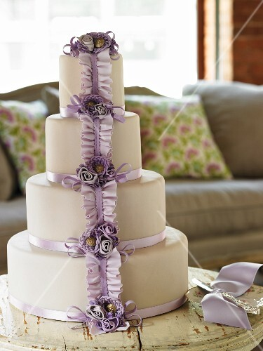 A Four Tier Wedding Cake with Lavender Ribbon and Flowers