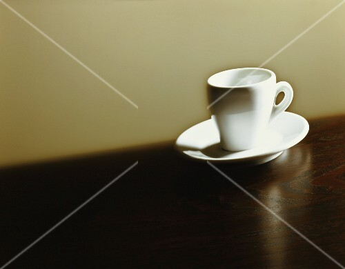 An espresso cup on a brown surface