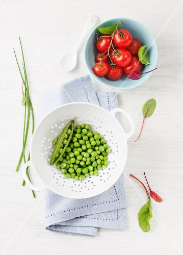Freshly shelled peas in a colander and vine tomatoes in a bowl