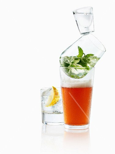 A stack of glasses with beer, mint and vodka with a gin and tonic next to it