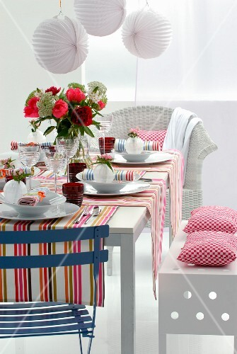 A table laid for a meal with colourful striped table runners and a summer bouquet under white paper lampions