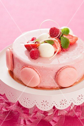 A strawberry and raspberry cake decorated with macaroons