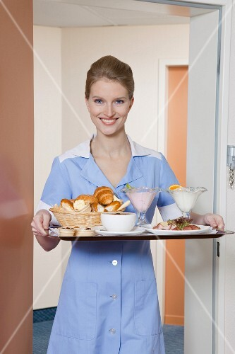 room maid holding tray with breakfast