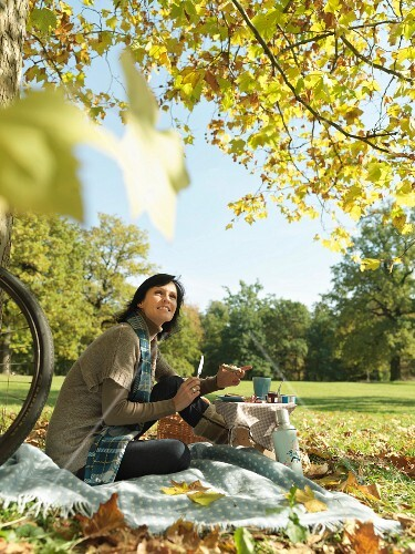 Woman enjoying Autumn picnic under trees