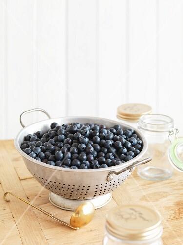 A colander of blueberries and jam jars
