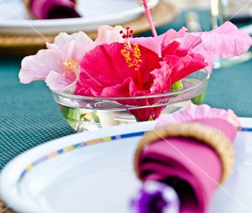 A place setting and a bowl of water hibiscus flowers