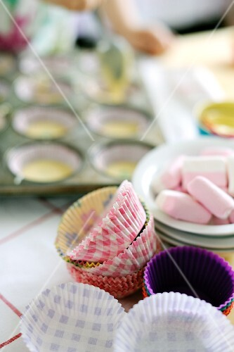 Young boy pouring cupcake mix into moulds