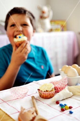 Young boy eating a cupcake