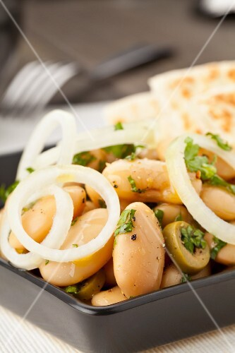 A white broad bean salad with olives and onions served with pita bread
