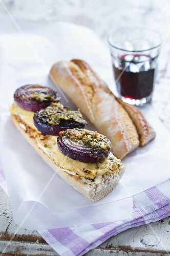 A chicken, mustard and red onion baguette sandwich
