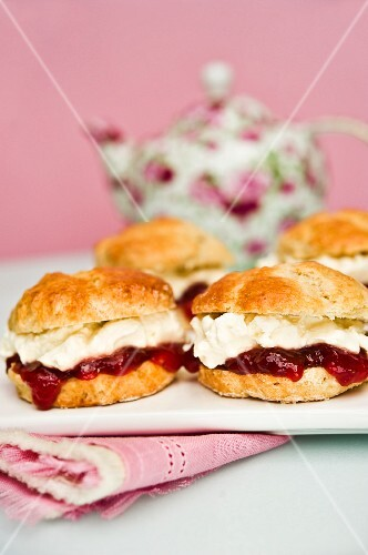 Scones with strawberry jam and cream with a pot of tea in the background