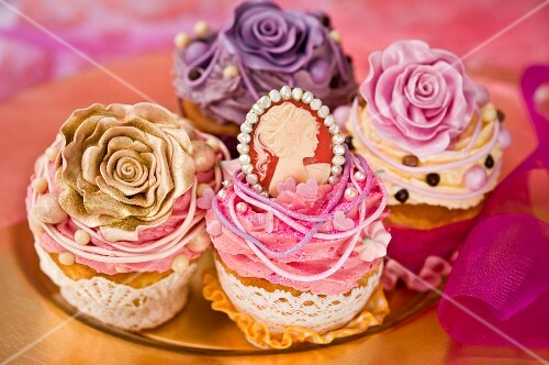 Celebratory cupcakes decorated with buttercream, sugar roses and a pendant
