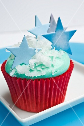 A Christmas cupcake decorated with blue stars