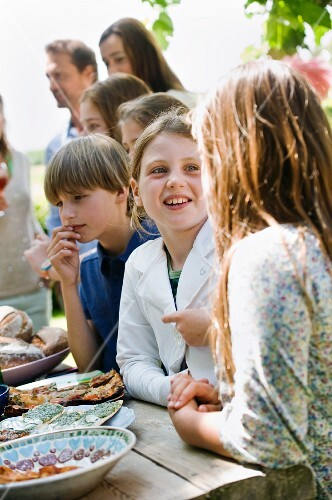 Children standing by the buffet at a garden party