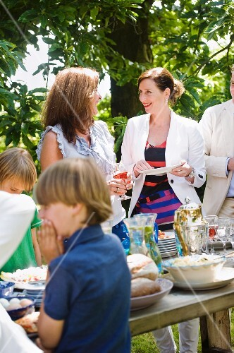 Children and adults standing around the buffet at a garden party