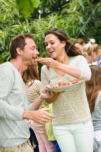 A woman feeding a man bruschetta at a garden party