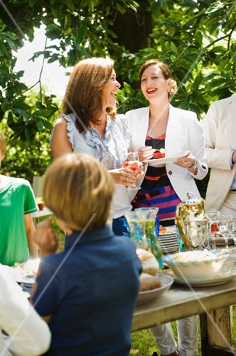 Young people chatting by the buffet at a garden party