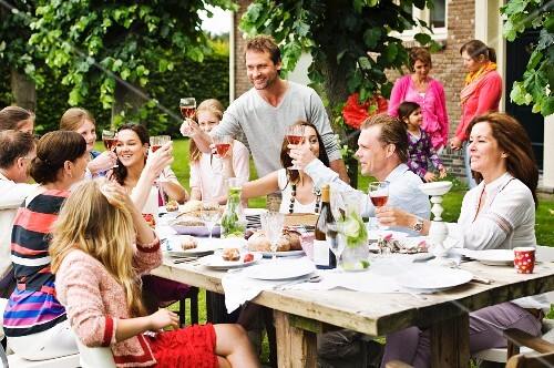 A convivial group raising their glasses at a garden party