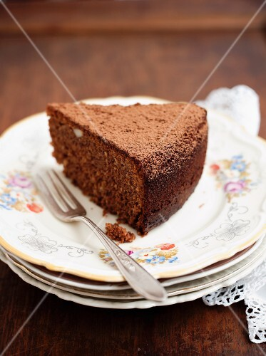 A slice of chocolate cake on a stack of plates