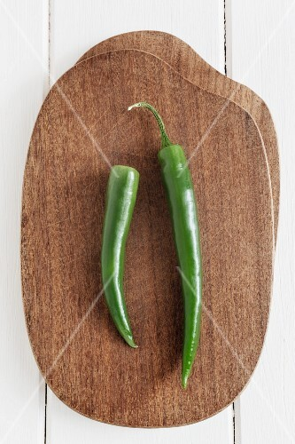 Two green chilli peppers on a chopping board