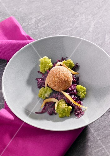 A dumpling on a bed of red cabbage and cauliflower