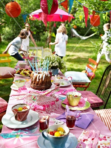 A birthday table in the garden with children playing in the background