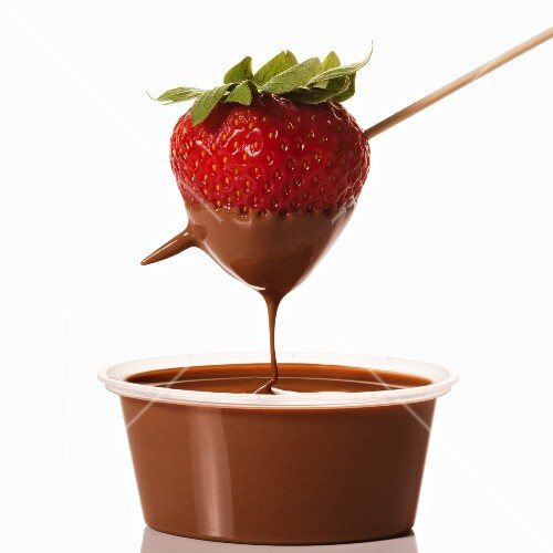 Strawberry Dipped in a Container of Chocolate Sauce