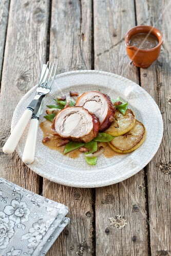 Sliced cochon de lait roulade with apples and beans
