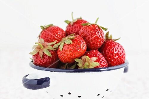 Fresh strawberries in an enamel colander