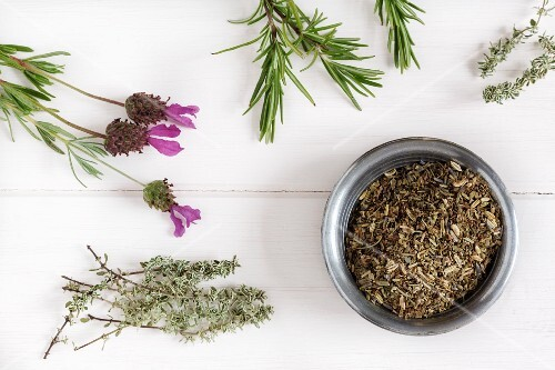 Herbs de Provence in a bowl surrounded by fresh herbs