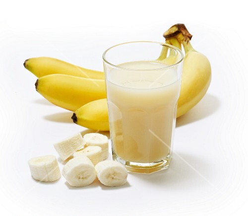 A glass of banana juice with bananas in the background and banana slices next to it