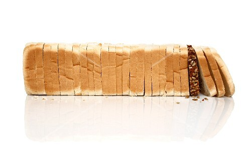 A slice of wholemeal bread in a row of white bread