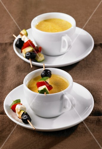 Carrot soup served in cups with vegetable kebabs