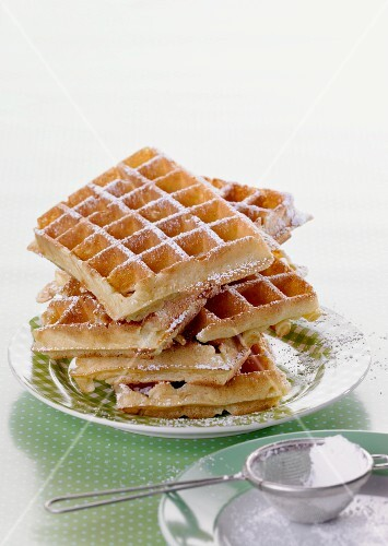 A stack of waffles dusted with icing sugar