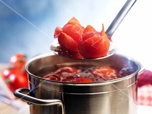 Tomatoes being blanched in boiling water