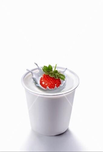 Splash created by a strawberry falling into yogurt