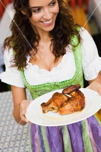 Junge Frau hält Teller mit Grillhähnchen