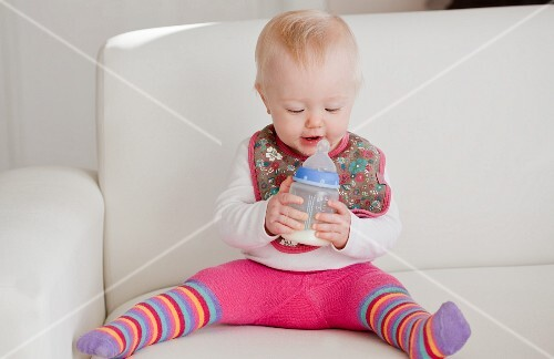 A baby sitting on a sofa with a bottle of milk
