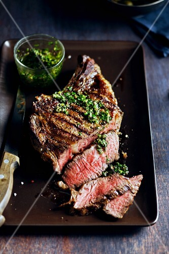 Partially Sliced Grilled Rib-Eye Steak with Herb Sauce