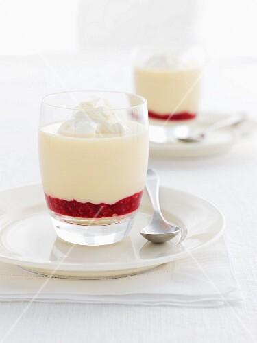 Layered cream dessert with white chocolate and strawberry sauce