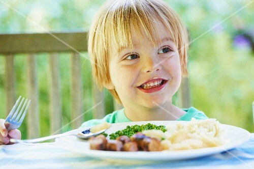 Smiling boy eating plate of food