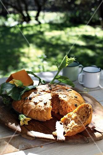 A loaf of pumpkin bread with pumpkin seeds, broken open