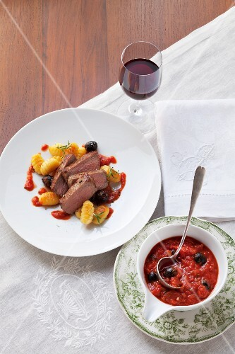 Beef steak with tomato and olive sauce and gnocchi