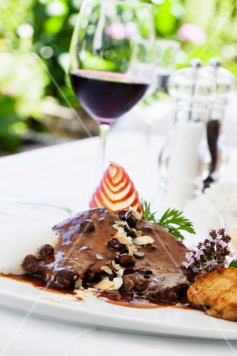 Rhenish Sauerbraten (marinated pot roast) with raisins and napkin dumplings and a glass of red wine