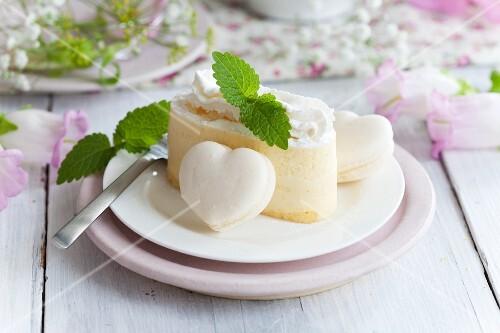 Slice of cream cake with macaron hearts