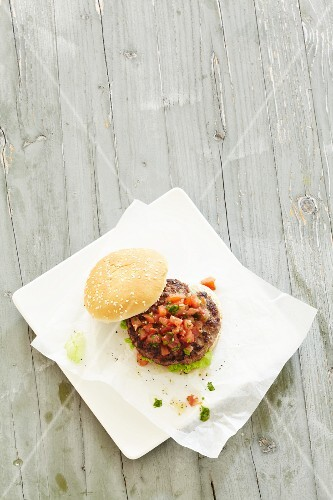 A hamburger with diced tomatoes