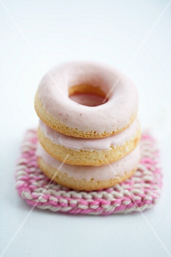 Doughnuts with pink sugar icing on a crocheted coaster